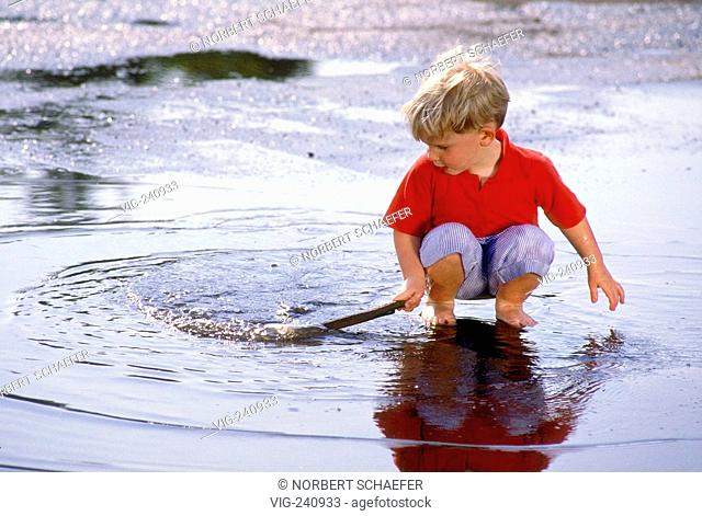 portrait, blond boy, 3 years, wearing red t-shirt plays bare feeted in a puddle  - GERMANY, 25/05/2003