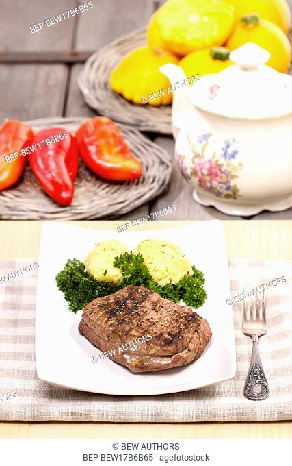 Roasted beef with potatoes, kettle and fresh vegetables in the background