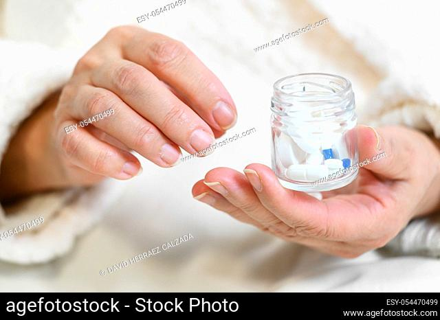 Elderly woman pouring pills from bottle on hand, closeup view