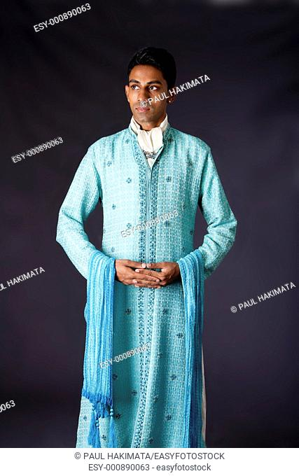 Beautiful authentic Indian hindu man in typical ethnic groom attire standing with hands together  Bangali male wearing a light blue agua decorated Dhoti with...