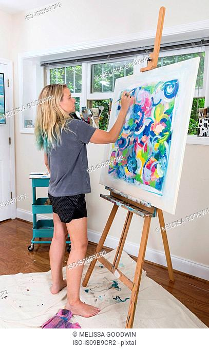 Female artist painting abstract canvas in studio