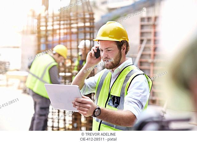 Engineer with digital tablet talking on cell phone at construction site