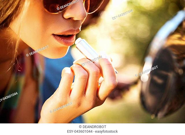 Picture of young woman sitting on scooter outdoors doing makeup of lips. Looking at mirror