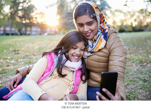 Muslim mother in hijab taking selfie with daughter in autumn park