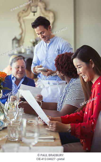 Waiter taking order of friends at restaurant table with menu
