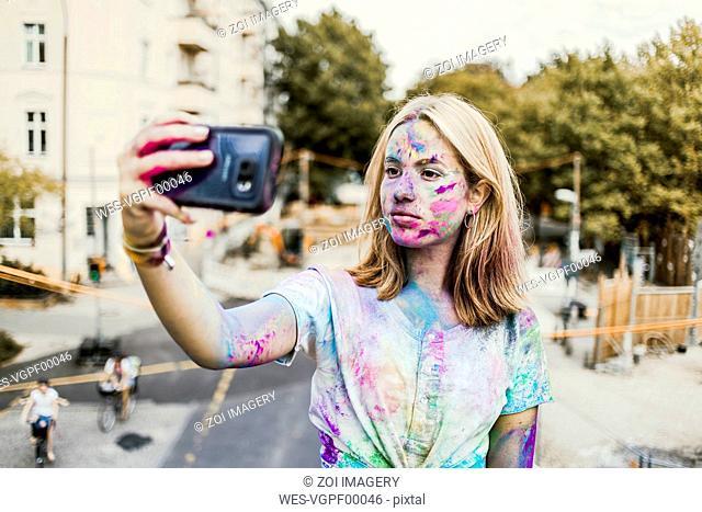 Gir Holi powder colours in her face, taking selfie, Germany