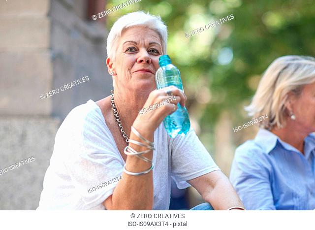 Senior woman sitting with bottle of water in city