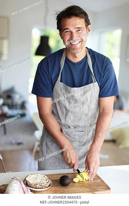 Portrait of smiling man cutting lemon in kitchen