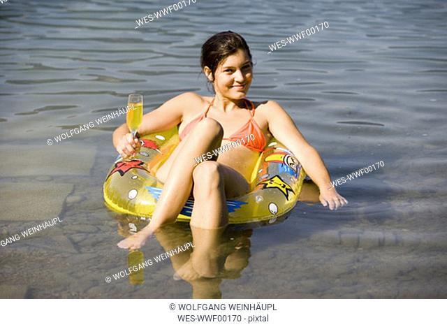 Young woman sitting in floating tyre, holding glass