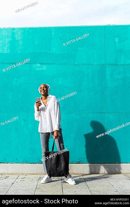 Businesswoman with headphones, standing in front of teal wall, using smartphone
