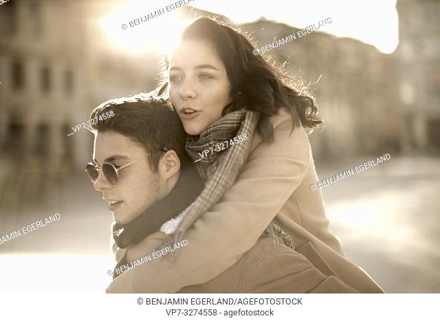 teenage woman embracing boyfriend from behind outdoors in sunlight in city, in Cottbus, Brandenburg, Germany