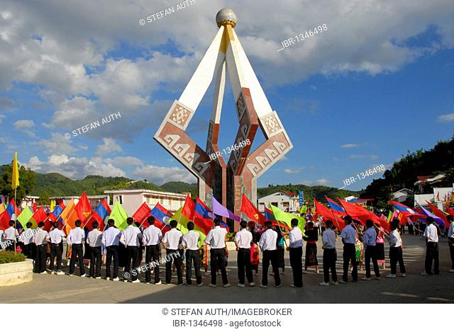 Parade, flag-bearers, young men of the Laotian Youth Organization Lao Youth with many colorful flags standing around a communist monuments, Xam Neua