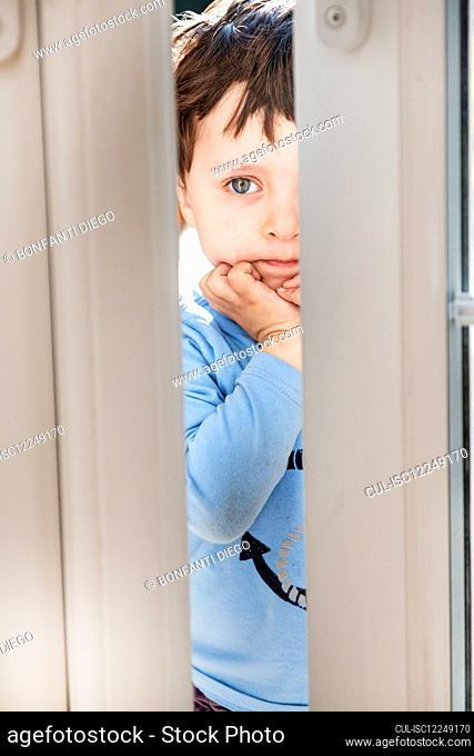 Portrait of boy wearing blue shirt peering through slightly open door
