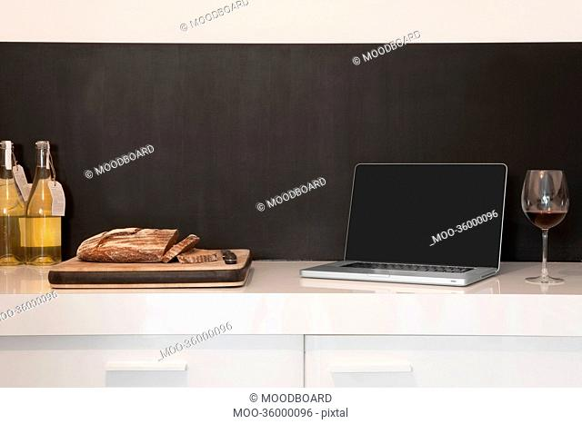 Laptop, wineglass and bread loaf on counter