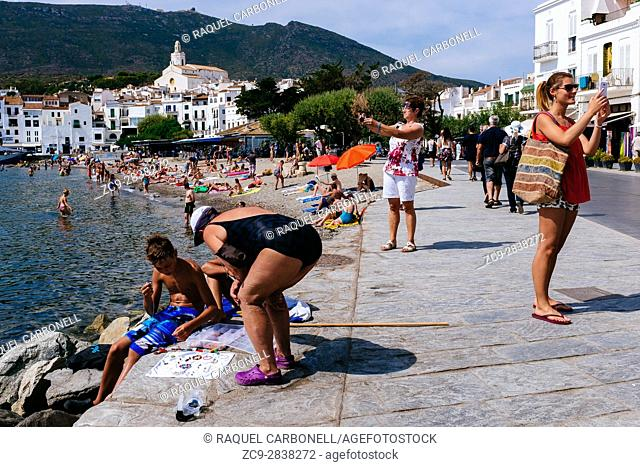 Tourists at the beach with the white village at back. Cadaqués, Alt Amporda, Gerona, Catalonia, France