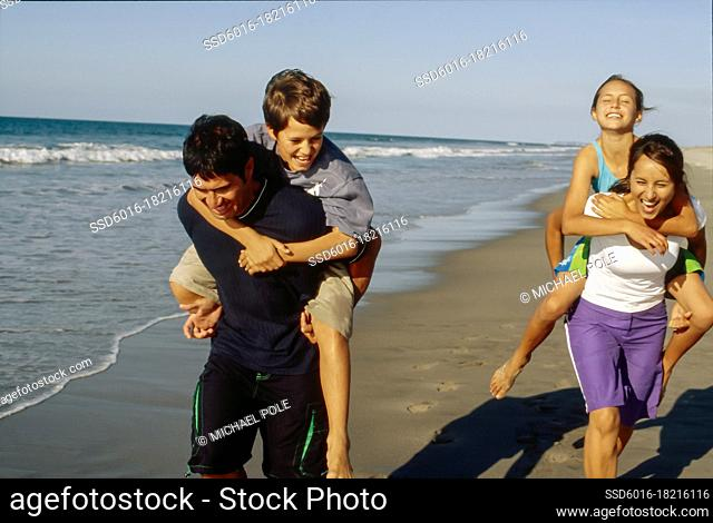 Mum and dad piggy backing kids and racing down the beach