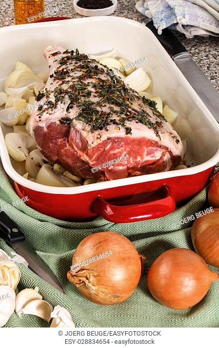raw leg of lamb with rosemary, crushed chili and olive oil marinade in a red and white enamel roasting pan