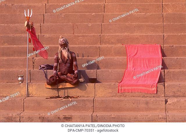 Indian Sadhu Hindu priest praying at river ganges in the oldest city Banaras now Varanasi , Uttar Pradesh , India