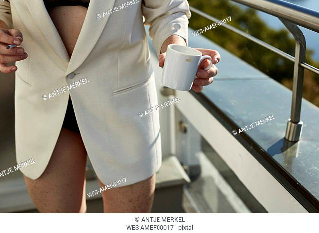 Mid-section of teenage girl standing on balcony with cigarette and cup of coffee