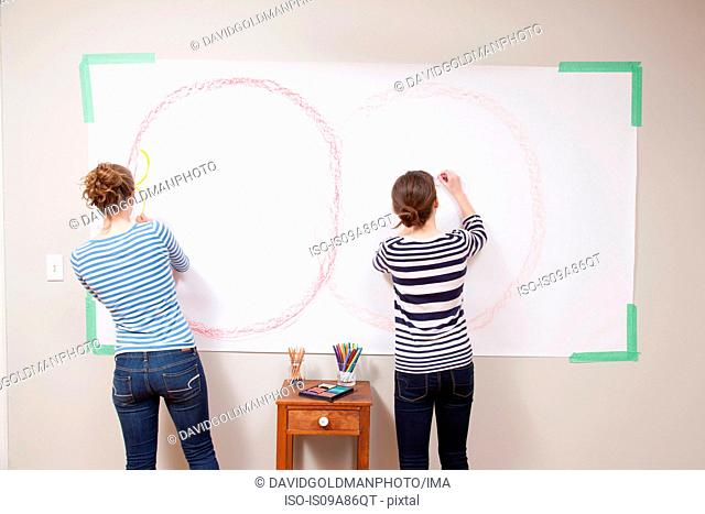 Girls drawing on wall