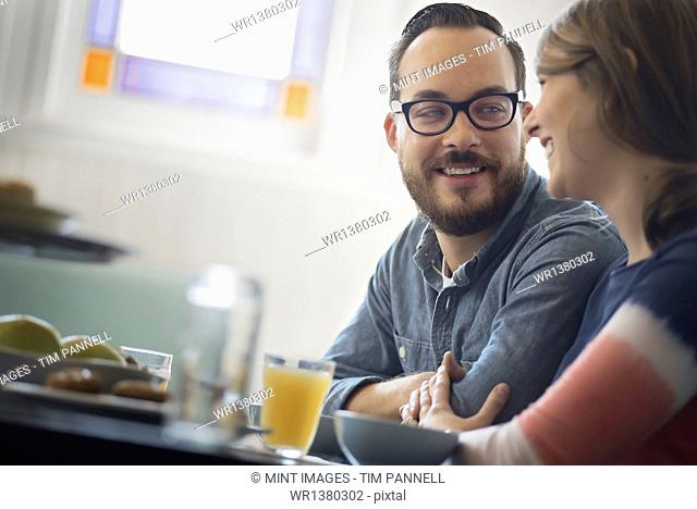 A couple sitting in a coffeeshop smiling and talking over a cup of coffee