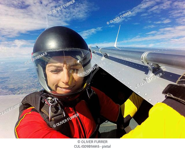 Portrait of female skydiver preparing to jump from aircraft