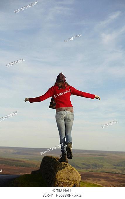Woman balancing on rock wall