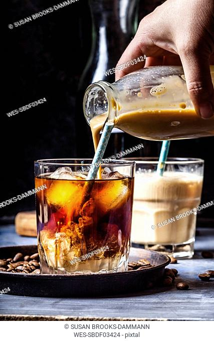 Hand pouring homemade vanilla flavoured coffee creamer into a glas with iced coffee