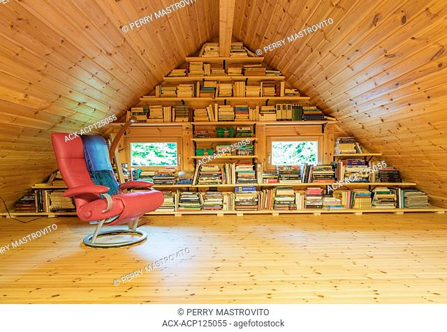 Red leather armchair with throw and books on wooden shelves in reading room on mezzanine inside a piece sur piece Scots pine log home, Quebec, Canada
