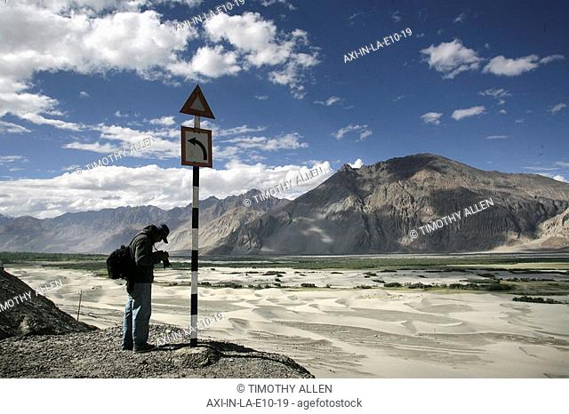 Tourist with camera on high altitude desert at Hundar