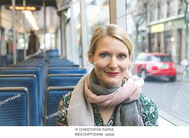 Portrait of smiling woman sitting in tramway