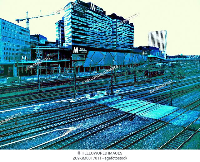 Blue tinted shot of multiple railway lines passing Mall of Scandinavia, Solna, Stockholm, Sweden, Scandinavia