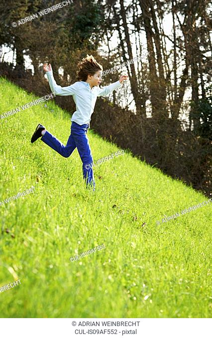 Young boy running down steep grassy field