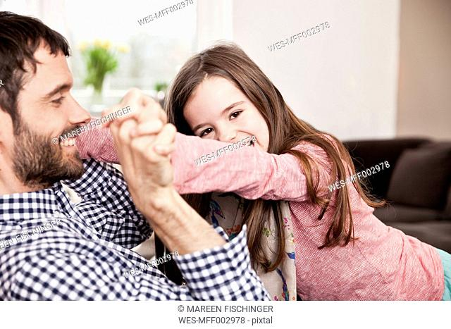 Daughter playfighting with her father on the couch