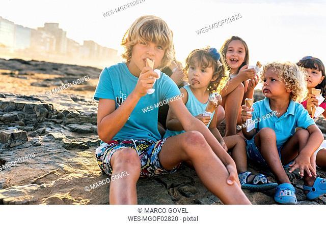 Group of six children eating icecream on the beach