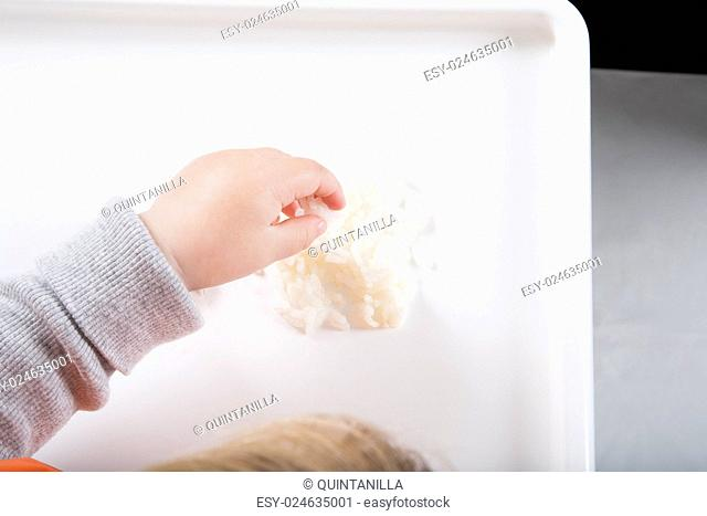blonde caucasian baby seventeen month age orange bib grey sweater eating rice with her hand in white high-chair