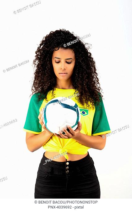 Portrait of a young supporter of the Brazil team watching a balloon