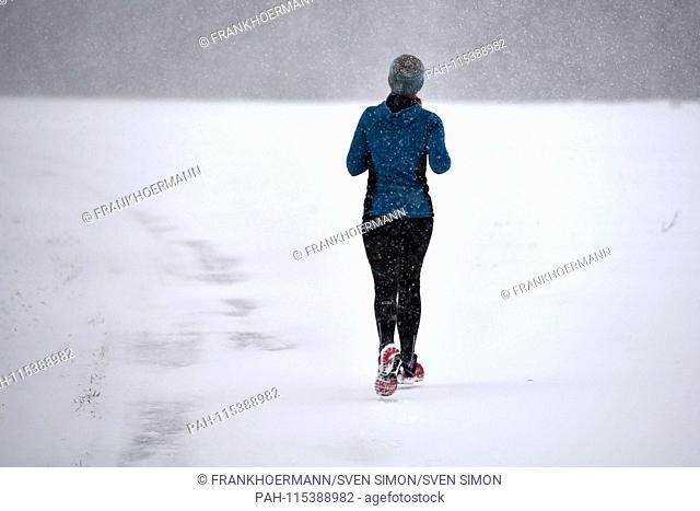 A jogger, Laueferin runs on snowy paths, Continuing snowfall on 05.01.2019, ensure snow chaos, traffic chaos, winter in Bavaria.   usage worldwide