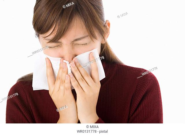 A young woman blowing nose on tissue