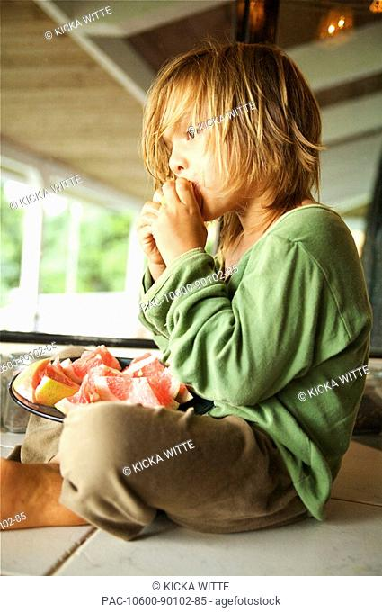 Hawaii, Kauai, Kilauea, Young boy sitting on porch eating grapefruit