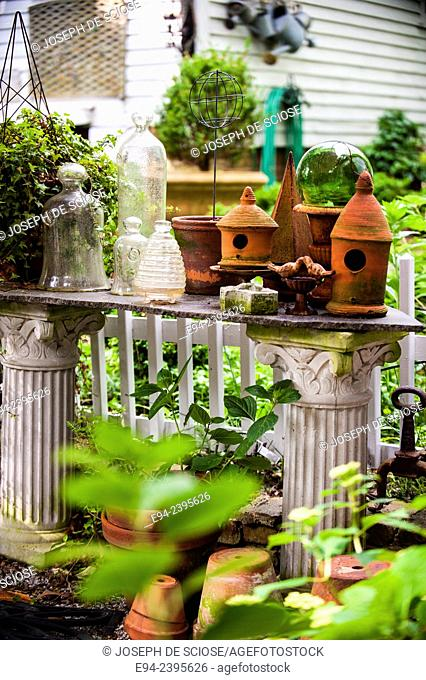 A garden vignette with cloches on a table with a potted boxwood on a pedestal and a house in the background