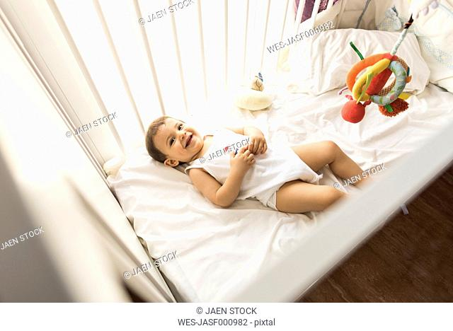 Portrait of happy baby boy lying in his cot