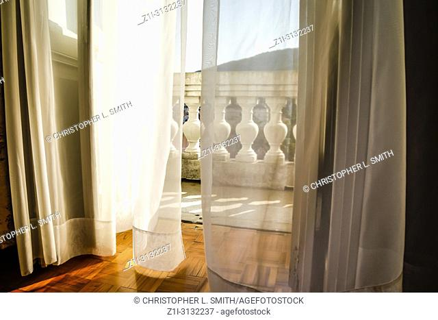 Behind net curtain drapes leads to the balcony at the Hotel Imperial in Opatija, Croatia