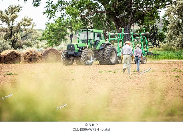 Rear view of male farmer and teenage boy walking over ploughed field