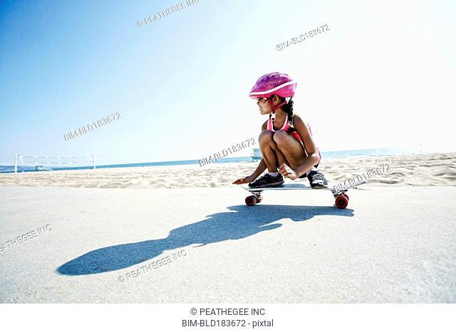 Mixed race girl riding skateboard at beach