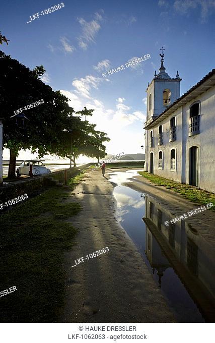 Morning sun in the rain filled Rua de Chapala, curch Iglesia de Nostra Senora das Dores, historic old town, Paraty, Costa Verde