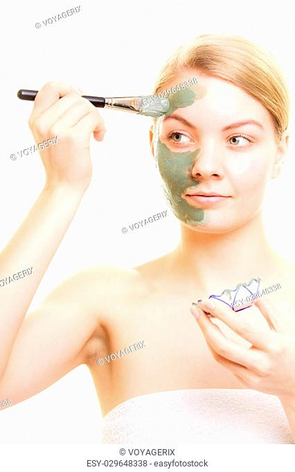 Skin care. Woman applying with brush clay mud mask on face isolated. Girl taking care of dry complexion. Beauty treatment