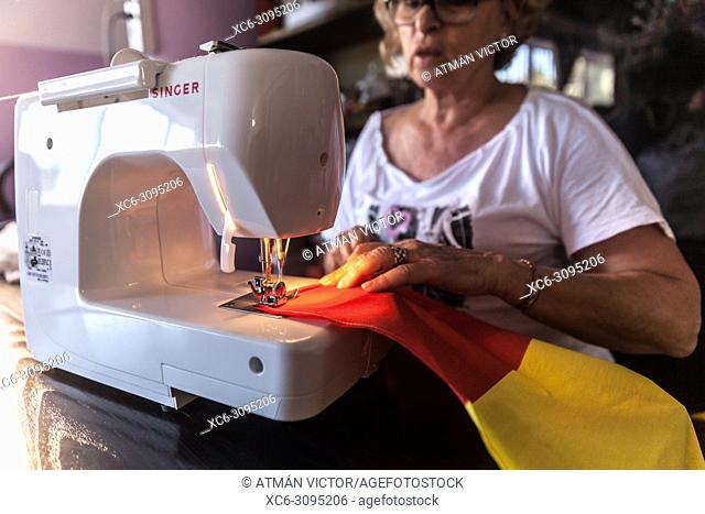 adult woman sewing the spanish flag with a SINGER brand sewing machine. Tenerife island