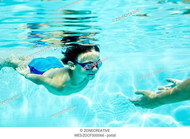 Young boy diving to mother, under water, swimming pool