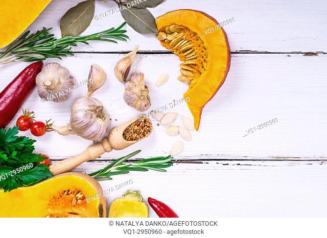 fresh slices of pumpkin and garlic with spices on a white wooden background, empty space on the right, top view